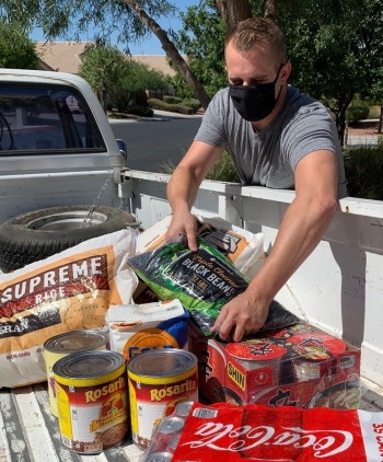 NNSA Nevada Field Office employee Tristan Dunn loads food in his truck after a door step pick-up.