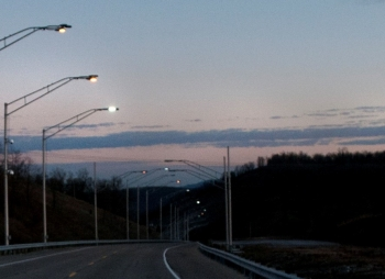 A road at dusk, lined with streetlights.