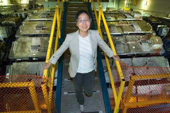 Lijuan Ruan stands atop the STAR detector at the Relativistic Heavy Ion Collider at Brookhaven National Laboratory. The silver Muon Telescope Detector components surrounding STAR's magnet detect muons, the decay products of J/psi particles.