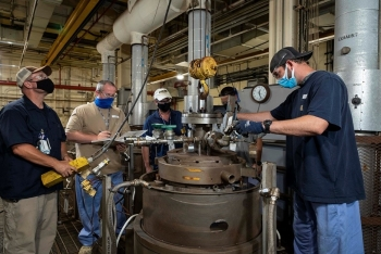 Y-12 National Security Complex chemical operators lower a reactor vessel into a furnace. The homogenization technology, developed by Y-12 scientists and engineers, is planned to be included in the site's proposed new Lithium Processing Facility.