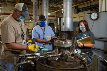 Y-12 chemical operators check a reactor vessel. The homogenization process takes place in the vessel, and several key parameters are checked and recorded hourly.