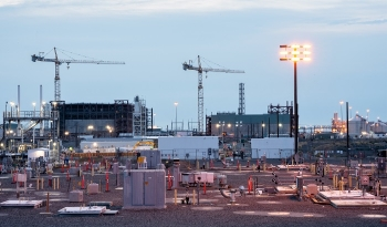 The white enclosures of the Tank-Side Cesium Removal (TSCR) system are visible adjacent to the Hanford Site's AP Tank Farm. In the background is the Waste Treatment and Immobilization Plant, where waste pre-treated by TSCR will be heated to 2,100 degrees.