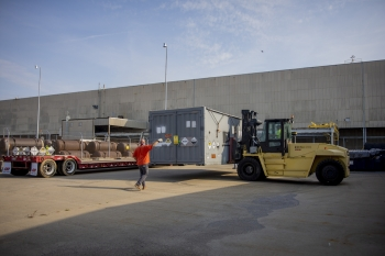 Paducah Site contractor maintenance mechanic Matt Wheeler spots Heavy Equipment Operator Ryan Jackson as a cold trap is lowered onto a shipping trailer outside the storage facility.
