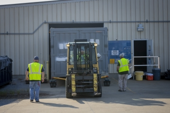 Paducah Site contractor operator Brad Story uses a forklift to move a cold trap out of the waste storage facility.