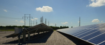 A solar photovoltaic plant with transmission power lines in the background