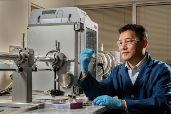 Sandia National Laboratories researcher Hongyou Fan holds a container enclosing gold supercrystals in front of a small-angle X-ray scattering instrument. Binary Solvent Diffusion for Fabrication of Large Nanoparticle Supercrystals won an R&D Award.