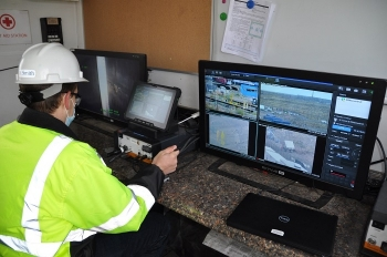 Devan Smith, an engineer for EM Richland Operations Office contractor CH2M HILL Plateau Remediation Company, monitors progress as workers prepare to stabilize three aging underground disposal structures by filling them with engineered grout.