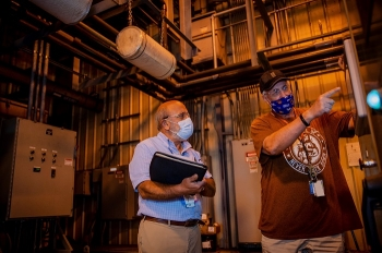 Paducah Site workers Joe Tarantino and Denver Parman discuss the operation and maintenance of the pump-and-treat equipment used at the site.
