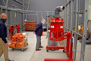 """EM Senior Advisor William """"Ike"""" White, right, ended his visit to the Hanford Site last week with a stop at a mock-up of a former plutonium processing laboratory located near Richland, Washington, and the Columbia River."""