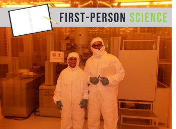 """Man and woman in clean room """"bunny suits"""" in front of machinery."""