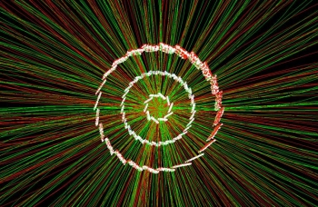 """A collision recorded by the Relativistic Heavy Ion Collider. The white points show """"hits"""" from particles emerging from the collision. Scientists use the hits to reconstruct charged particle tracks (red and green lines) and measure particles' abundance."""