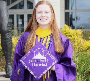 Woman stands smiling with her cap and gown.