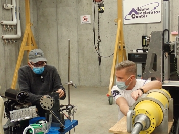 Fluor Idaho Engineer Kevin Young, left, and Idaho Accelerator Center Imaging Laboratory Director Mike Smith prepare calcine retrieval project components for radiation testing with a high-powered X-ray generator.