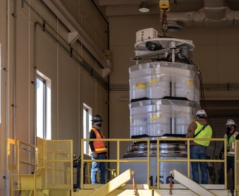 Workers at the Radioassay and Nondestructive Testing facility at the Los Alamos National Laboratory load the first comingled transuranic waste shipment from EM and the National Nuclear Security Administration.