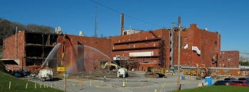 Crews began knocking down Building 9210, at left, at Oak Ridge in November last year. Demolition on the massive Building 9207, at right, will begin later this month.
