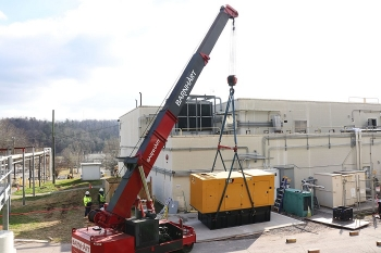 Workers install a backup diesel generator at Building 2026. If there is a loss of power, it can produce enough power to maintain operation of equipment necessary to process uranium-233 at Oak Ridge.