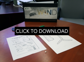 Box on a table labeled wind with two pieces of paper with computer-generated wind turbine drawings and instructions.