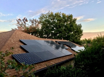 sun sets over a rooftop solar installation
