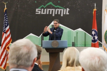 Rick Perry standing behind a 3D printed podium.