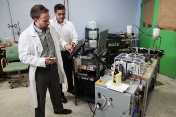 Photo of two men in lab coats working on a magnetocaloric system.