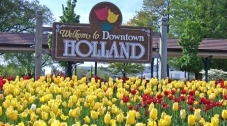 """Sign that says """"Welcome to downtown Holland,"""" with tulips in the foreground."""