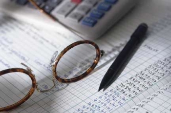 Photo of an accounting sheet, reading glasses and mechanical pencil