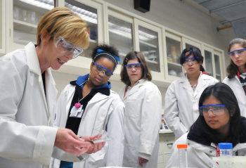 Group of scientists wearing lab coats and safety glasses, examining some items in a lab.