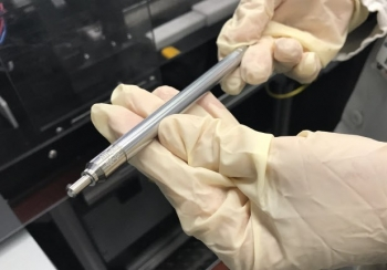 Picture of hands holding a test fuel pin designed by Framatome.