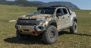 A Chevy truck that is powered by a battery and fuel cells with mountains in the back drop.
