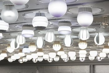 Different shapes of lighting fixtures using LED lights hang from the ceiing.