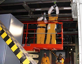 Workers assess piping in preparation for future demolition.