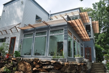 Photo of the exterior of a house, showing a glassed-in patio in the forefront.