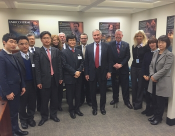 Photo of a group of people in business suits standing in a meeting room, facing the camera.