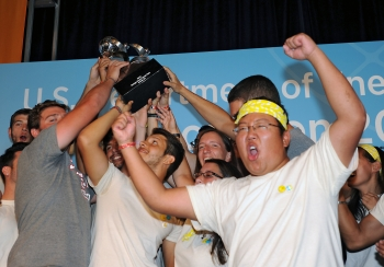 Solar Decathlon winners cheer and hold up a trophy.