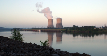 A photo of two cooling stacks in the distance with a river in the foreground