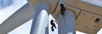 Two men hanging from a wind turbine as they work to prepare the turbine.