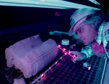 A scientist uses ultra-violet light to study how fluids move through rock
