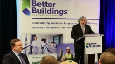 The former Secretary of Energy speaking at a podium with a backdrop of the Better Buildings program.