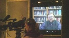 Photo of a woman with a video camera in a room set up in front of a screen showing a man facing the camera via Skype.