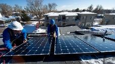 Men installing solar panels on a roof.
