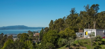 An expanse of trees and a home on a cliff, with a lake and mountains beyond.