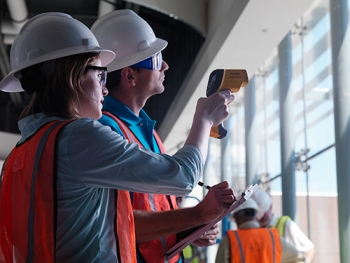 A man and a woman in hard hats working in a building, in front of windows.