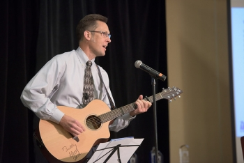 Photo of Eric Werling playing a guitar at a microphone during an event.