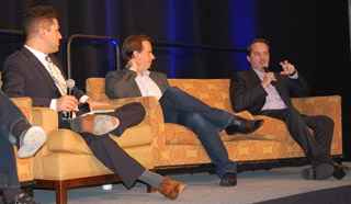 Three men in business suits seated on couches, addressing an audience during a panel.