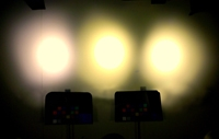 Photo of a dark wall with three LED lights shining on it.