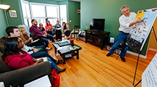 A group of people seated in a casual living room scene, focused on a man presenting to them with a flipchart.