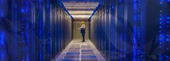 A photo of a person standing at the far end of a row of computer servers.
