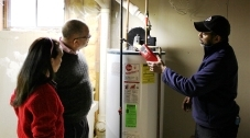 A person examining a hot water heater while another person stands nearby.