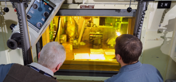 Photo of two men, backs to the camera, looking through a tinted window at a part of the fuel cycle process.