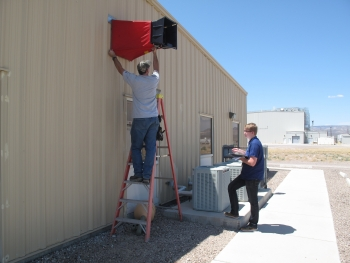 Two men take air-flow measurements at the Field Engineering Building